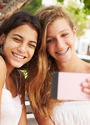 Two girls taking selfie one has braces