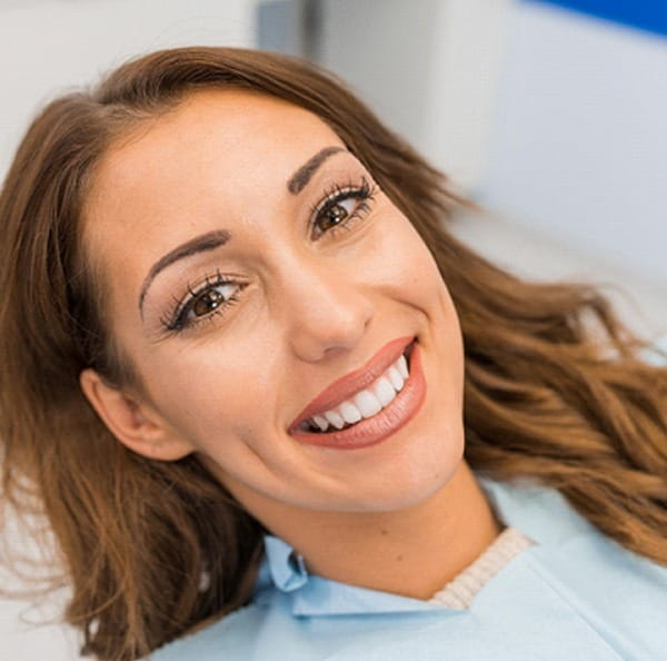 Woman smiling with straight teeth at dental appointment