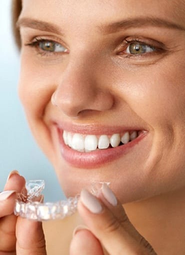 Woman smiling while putting in clear aligners