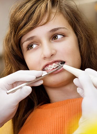 Teen girl having bracket repaired