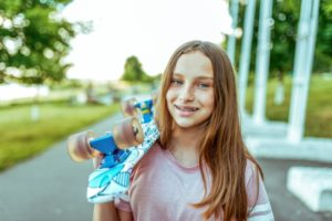teen with traditional braces holding a skateboard over their shoulder