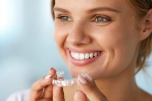Smiling woman holds Invisalign in Glenpool