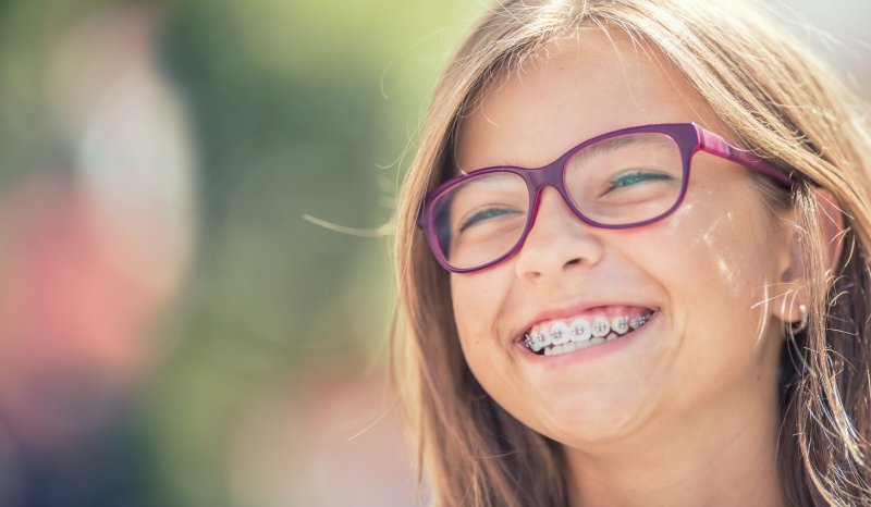 a young girl outside wearing glasses and braces while smiling