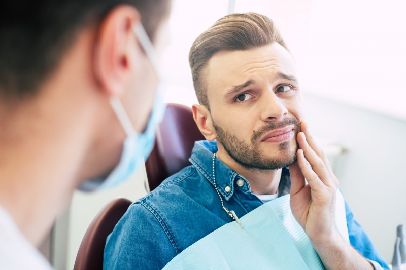 Male patient talking to dentist about toothache