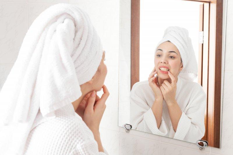Woman checking her teeth in bathroom mirror