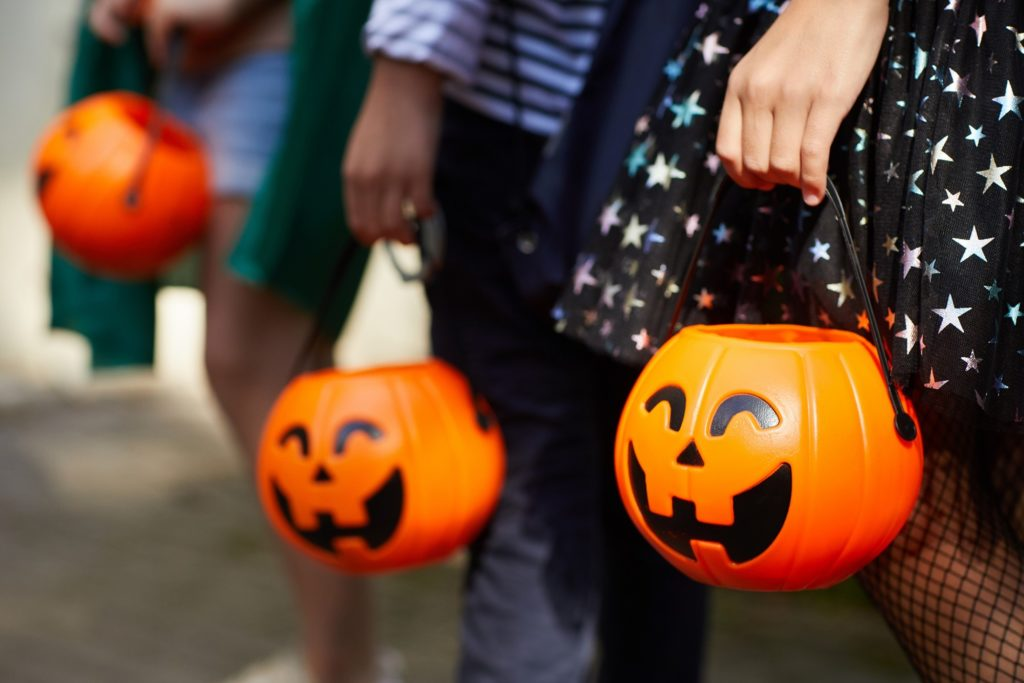 Closeup of children holding jack-o-lantern candy bags